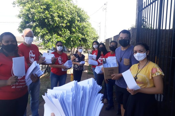 Voluntários católicos distribuem cartas de carinho para moradores na região